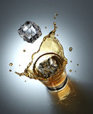 Ice cube splashing in a glass full of liquid Royalty Free Stock Photos