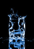 Ice cube splashing into glass of water Stock Photo