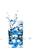 Ice cube splashing into glass of water Royalty Free Stock Photos