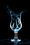 Ice cube splashing into glass of water Royalty Free Stock Photography
