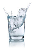 Ice cube splashing into glass with water Royalty Free Stock Photo