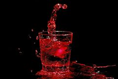 Ice cube splashing into a glass of wine Stock Images