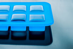 Ice cube tray with ice on the table Stock Photos