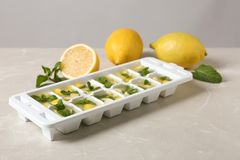 Ice cube tray with mint, lemon and water. On grey table stock photos