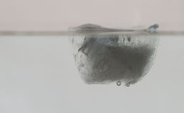 Ice cube in water. Floating ice cube in water royalty free stock photography