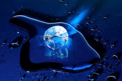 Ice cube in water puddle Royalty Free Stock Photos