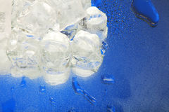 Ice cubes. Frozen ice cubes on blue background with water drops Royalty Free Stock Images