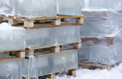 Ice cubes. Huge ice cubes stacked on the industrial pallets Royalty Free Stock Photo