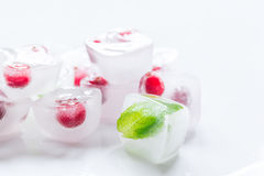 Ice cubes with berries and mint for summer drink on white background Stock Photography