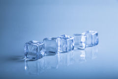 Ice cubes on blue background studio shot photo Royalty Free Stock Photography