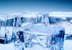 Ice cubes on blue background Stock Photography