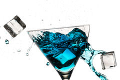 Ice cubes breaking martini glass filled Royalty Free Stock Images