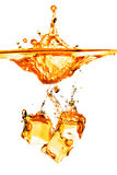 Ice cubes dropped into orange water with splash isolated on whit Royalty Free Stock Image