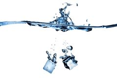 Ice cubes dropped into water with splash Royalty Free Stock Photography