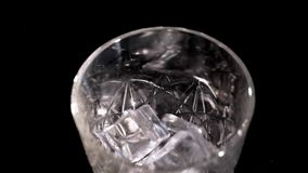 Ice cubes fall into a glass. Slow motion stock video