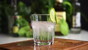 Ice cubes fall in glass of soda or mineral water slow motion with food background. Slice of lime on the glass. stock footage