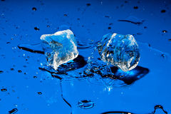 Ice cubes falling on blue surface Royalty Free Stock Images