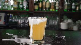 Ice cubes falling into mug full of beer. Slow motion. Foam and splashes on bar counter. nutrition and drink concept