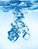 Ice cubes falling under water royalty free stock photography