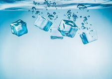 Ice cubes falling under water Stock Images
