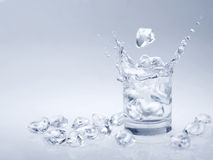 Ice cubes falling in water. Ice cubes falling into a glass of water Royalty Free Stock Images