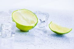 Ice cubes with fresh lime isolated on white Royalty Free Stock Photography