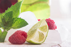 Ice cubes, fresh raspberries, mint and lime. On a wooden table Royalty Free Stock Photography