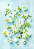 Ice cubes with frozen mint leaves inside on blue Turquoise background, top view Stock Photo