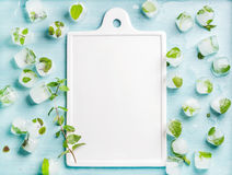 Ice cubes with frozen mint leaves inside on blue Turquoise background and white ceramic board in center, copy space Royalty Free Stock Image