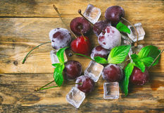 Ice cubes, frozen ripe cherry, mint leaves Stock Photo