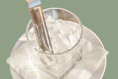 Ice cubes in a glass on a plate with napkin  on the grey Royalty Free Stock Photos