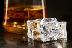 Wet square ice cubes. Ice cubes with glass of whiskey behind on black rustic background royalty free stock images