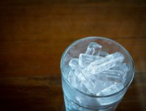 Ice cubes in glass on a wooden dark background. royalty free stock images