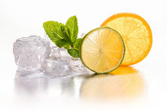 Ice cubes, lime and orange. Royalty Free Stock Photography