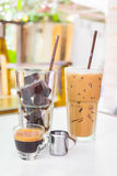 Ice cubes made from black coffee with small cup of hot espresso Stock Images