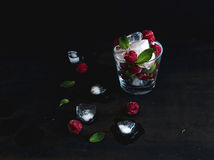 Ice cubes with mint leaves and frozen raspberry in glass on grunge dark background Stock Photo