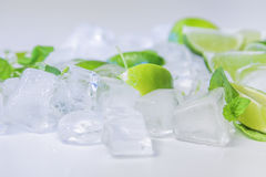 Ice cubes with mint and lime on white Royalty Free Stock Photos