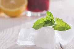 Ice cubes, mint and soft drink. On a wooden table Stock Images