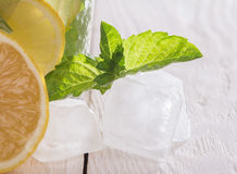 Ice cubes, mint and soft drink. On a wooden table Royalty Free Stock Photo
