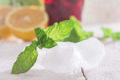 Ice cubes, mint and soft drink. On a wooden table Royalty Free Stock Photos