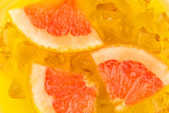 Ice cubes in orange and grapefruit juice Stock Images