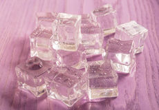 Ice cubes on purple colored  wooden background Royalty Free Stock Image
