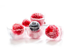 Ice cubes with raspberry and blueberry on white background Stock Photos
