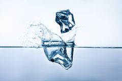 Ice cubes splashing into clear water. Two ice cubes splashing into clear water, closeup, frontview Stock Images