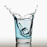 Ice cubes splashing into glass of water Stock Images