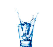 Ice cubes splashing into glass of water, isolated on white Stock Photos