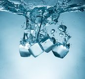 Ice cubes splashing into water Royalty Free Stock Photography