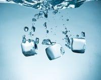 Ice cubes splashing into water. Stock Photo