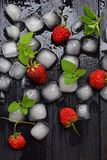 Ice cubes, strawberries and mint leaves on a black wooden background. Food background.  Stock Photos