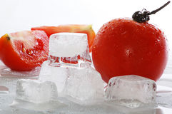 Ice cubes and tomato. Five ice cubes melted in water and tomato royalty free stock images